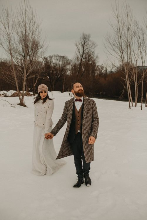 Bride and groom in jumper and overcoat holding hands at snow wedding elopement