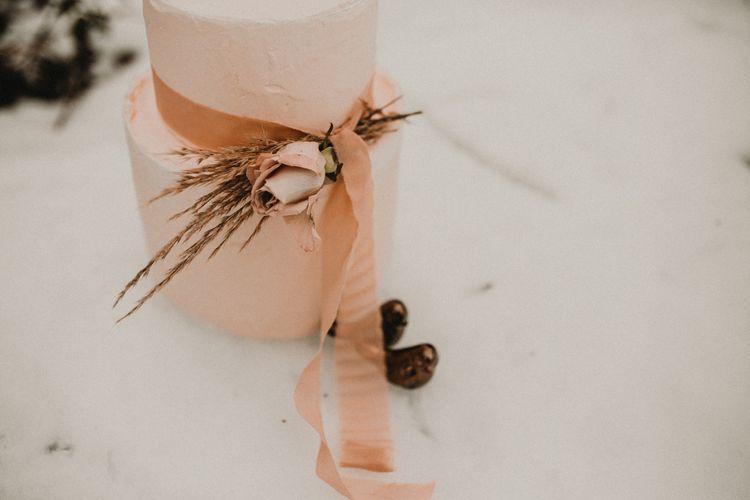 Blush pink wedding cake tied with ribbon
