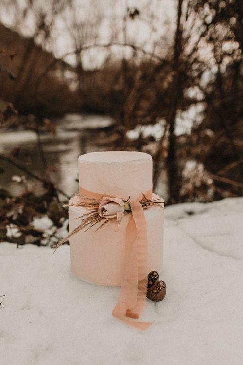 Elegant pink wedding cake with ribbon decor at snow wedding
