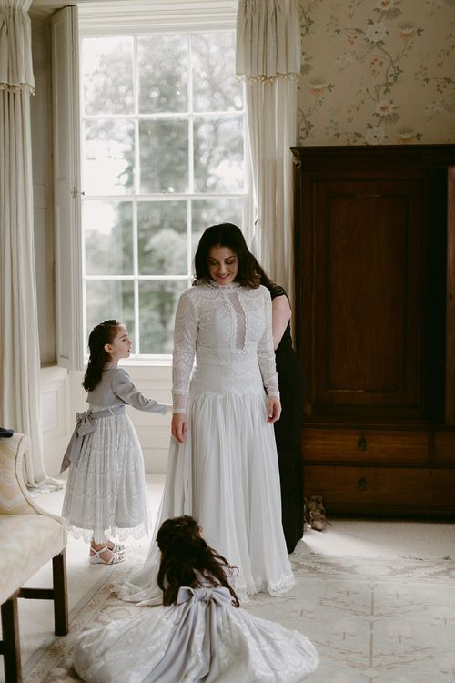 Bride in Homemade Wedding Dress with Lace Long Sleeves and High Neck Getting Ready