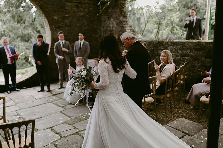 Bride Walking Down the Aisle in a Homemade Wedding Dress with Lace Bodice and Long Sleeves