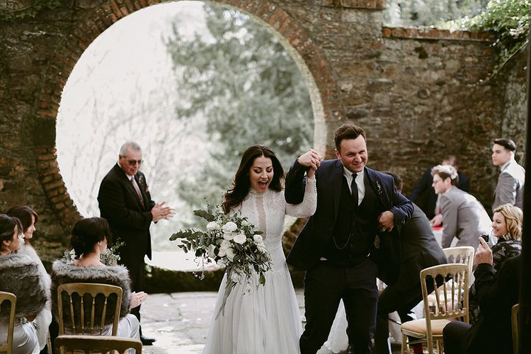 Bride in a Homemade Wedding Dress with Lace Bodice and Long Sleeves and Groom in Navy Suit Walking Up the Aisle