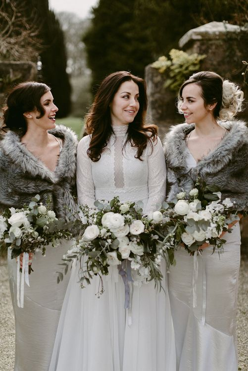 Bridal Party and Bridesmaids in Grey Satin Dresses with Fur Stoles and Bride in a Homemade Wedding Dress with Lace Bodice and Long Sleeves