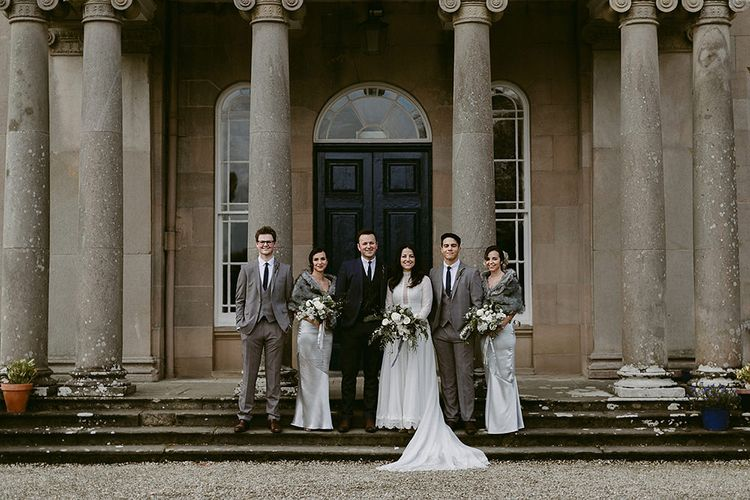 WeddingParty with Bridesmaids in Grey Satin Dresses & Fur Stoles, Bride in a Homemade Wedding Dress with Lace Bodice and Long Sleeves, and Groomsmen in Grey Suits
