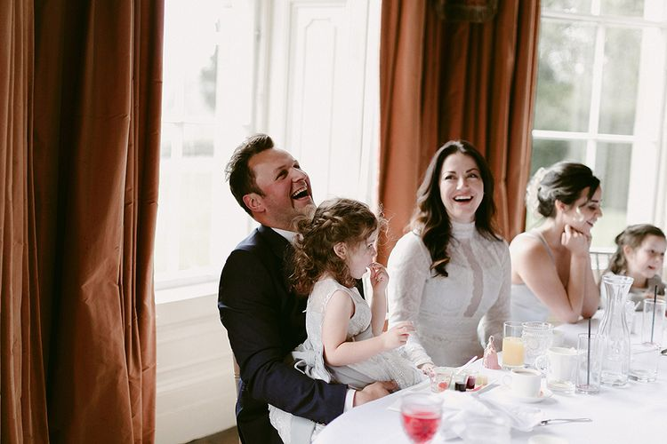 Bride in Homemade Wedding Dress with High Neck and Long Sleeves Laughing During The Speeches with Her Groom in Zara Suit