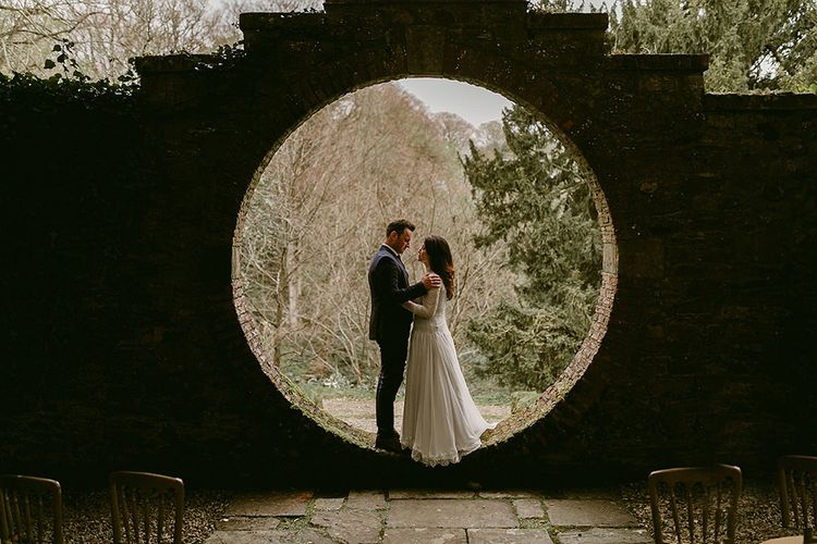 Bride in Homemade Wedding Dress with Lace Long Sleeves and High Neck and Groom in Navy Zara Suit
