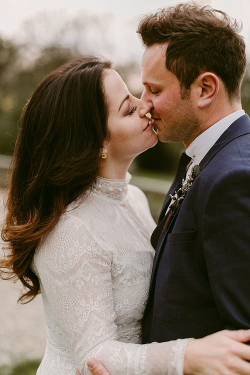 Bride in Homemade Wedding Dress with Lace Long Sleeves and High Neck and Groom in Navy Zara Suit Kissing