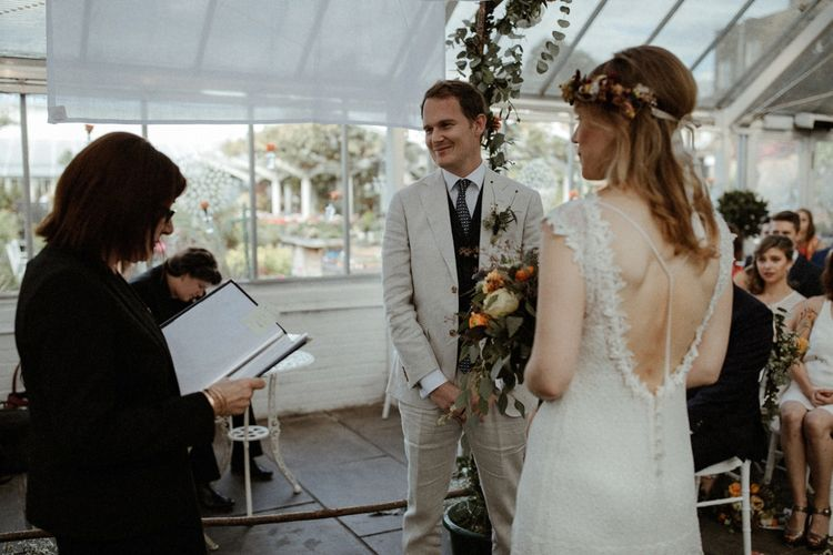Wedding Ceremony   Boho Bride in Lace Sally Lacock Gown with Flower Crown   Groom in Beige Suit Supply Suit    Orange, White & Green Boho Wedding at Clifton Nurseries London    Olivia & Dan Photography
