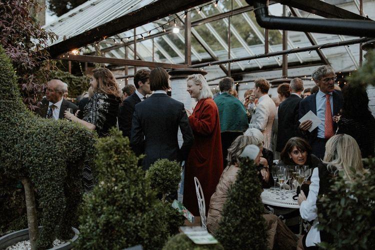 Glasshouse Reception   Orange, White & Green Boho Wedding at Clifton Nurseries London    Olivia & Dan Photography