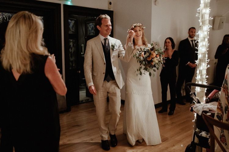 Reception Entrance   Boho Bride in Lace Sally Lacock Gown with Flower Crown   Groom in Beige Suit Supply Suit    Orange, White & Green Boho Wedding at Clifton Nurseries London    Olivia & Dan Photography