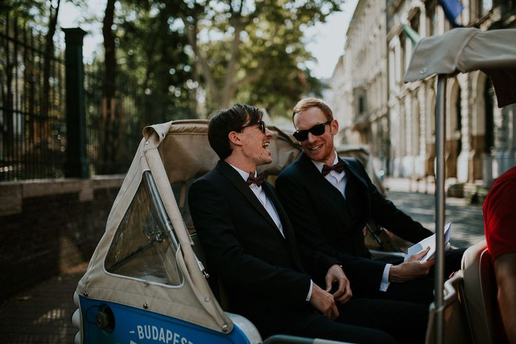 Groom in Black Three-Piece Suit from Hackett with Burgundy Bow Tie from Zara | Groomsman in Black Tuxedo Suit from Moss Bros. with Burgundy Bow Tie from Zara | Tuk Tuk Wedding Transport | Budapest Wedding with Giant Bridal Bouquet, Tuk Tuks and Cadillac | Jágity Fanni Fotográfus