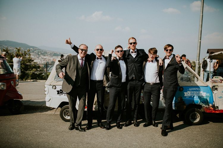 Groom in Black Three-Piece Suit from Hackett with Burgundy Bow Tie from Zara | Groomsmen in Black Tuxedo Suits from Moss Bros. with Burgundy Bow Ties from Zara | Tuk Tuk Wedding Transport | Budapest Wedding with Giant Bridal Bouquet, Tuk Tuks and Cadillac | Jágity Fanni Fotográfus