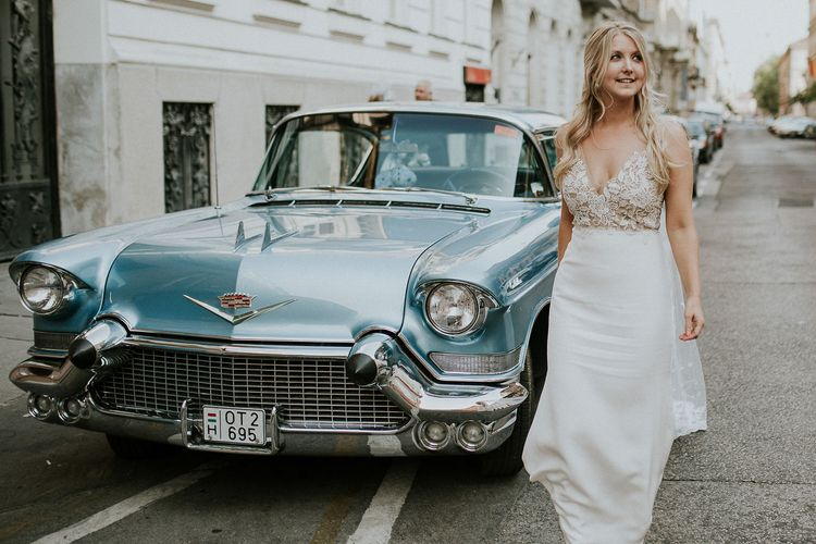 Vintage Blue Cadillac Wedding Car | Bride in Lila Gown by Alexandra Grecco with Fitted Silk Crepe Skirt and Sheer Italian Tulle Bodice Covered in Floral Lace Applique | Budapest Wedding with Giant Bridal Bouquet, Tuk Tuks and Cadillac | Jágity Fanni Fotográfus