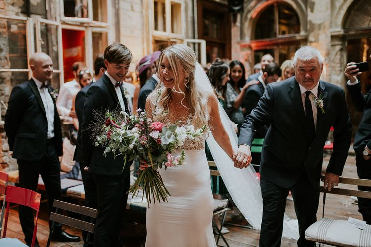 Bride in Lila Gown by Alexandra Grecco with Fitted Silk Crepe Skirt and Sheer Italian Tulle Bodice Covered in Floral Lace Applique | Theia Bridal Veil with Petal Detail | Oversized  Bouquet with Pink, Red and White Flowers and Foliage | Budapest Wedding with Giant Bridal Bouquet, Tuk Tuks and Cadillac | Jágity Fanni Fotográfus