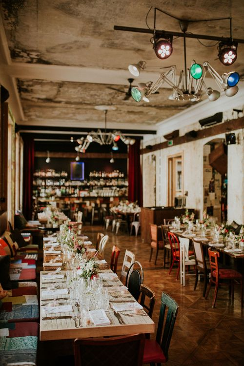 Wedding Reception at Brody Studios in Budapest, Hungary | Long Wooden Tables | Mismatched Chairs | Colourful Lights | Budapest Wedding with Giant Bridal Bouquet, Tuk Tuks and Cadillac | Jágity Fanni Fotográfus