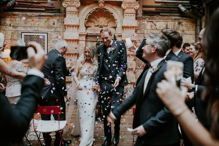 Bride in Lila Gown by Alexandra Grecco with Fitted Silk Crepe Skirt and Sheer Italian Tulle Bodice Covered in Floral Lace Applique | Theia Bridal Veil with Petal Detail | Groom in Black Three-Piece Suit from Hackett with Burgundy Bow Tie from Zara | Colourful Confetti | Wedding Ceremony at Brody Studios | Budapest Wedding with Giant Bridal Bouquet, Tuk Tuks and Cadillac | Jágity Fanni Fotográfus
