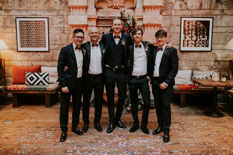 Groom in Black Three-Piece Suit from Hackett with Burgundy Bow Tie from Zara | Groomsmen in Black Tuxedo Suits from Moss Bros. with Burgundy Bow Ties from Zara | Budapest Wedding with Giant Bridal Bouquet, Tuk Tuks and Cadillac | Jágity Fanni Fotográfus