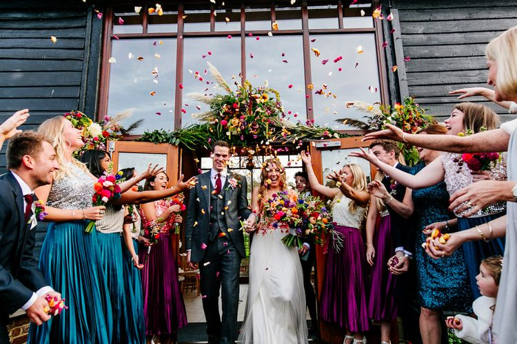 Confetti Moment |  Bride in Red & White Joanne Fleming Design Wedding Dress | Groom in Suit Supply | Colourful Alternative Winter Wedding at Upwaltham Barns, Sussex | Epic Love Story Photography