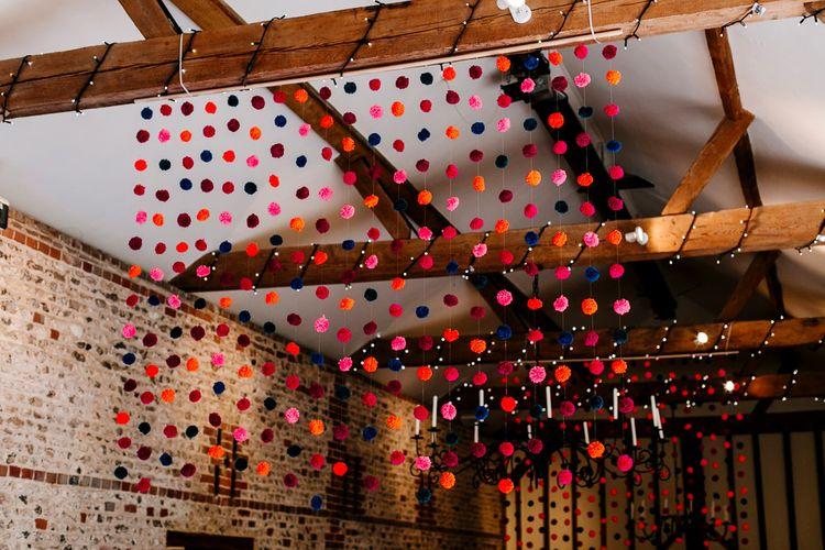 Hanging Pom Pom Wedding Decor | Colourful Alternative Winter Wedding at Upwaltham Barns, Sussex | Epic Love Story Photography