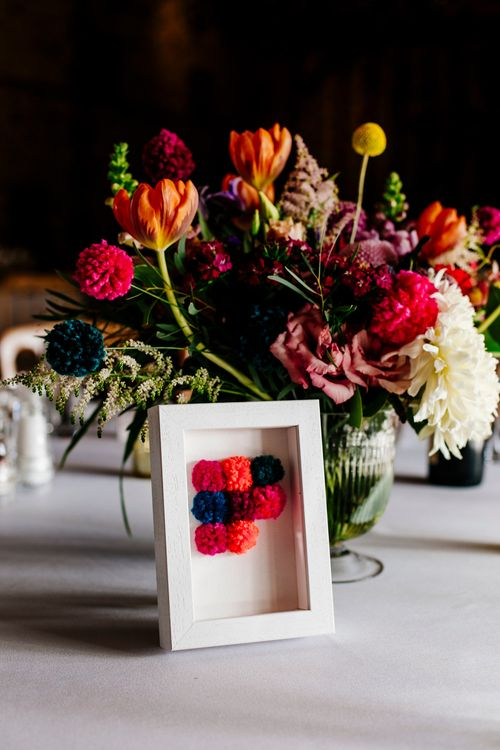 Table Centrepiece with Pom Pom Table Number | Colourful Alternative Winter Wedding at Upwaltham Barns, Sussex | Epic Love Story Photography