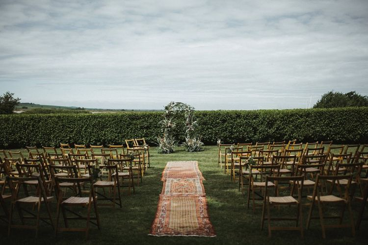 Outdoor Wedding Ceremony Setup with Floral Arch and Rug Aisle