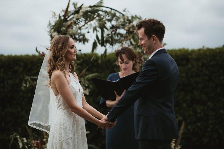 Bride In Rue De Seine Dress and Groom in Navy Suit Exchanging Vows