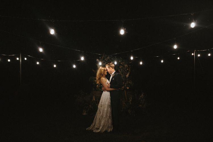 Bride and Groom Standing Under Festoon Lights