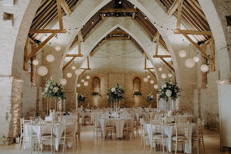 Wedding breakfast decor at Tithe Barn Petersfield with tall floral centrepieces