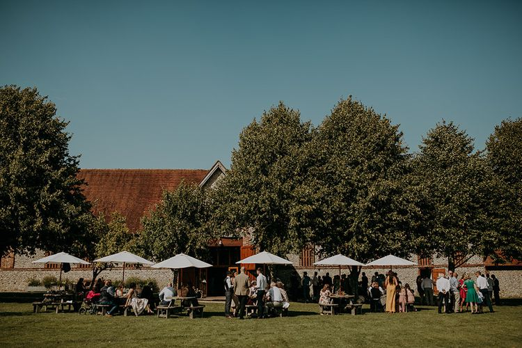 Guests enjoy drinks outside Tithe Barn Petersfield wedding venue