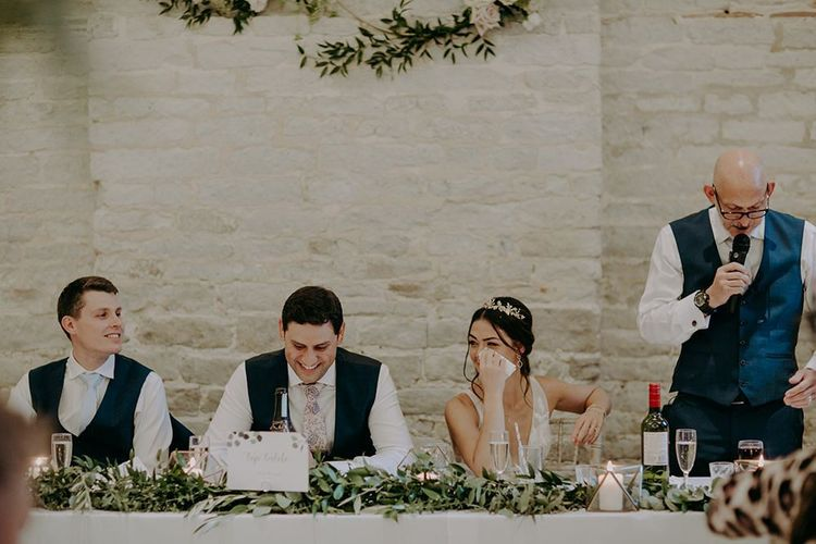 Bride and groom wipe tears at emotional wedding speeches