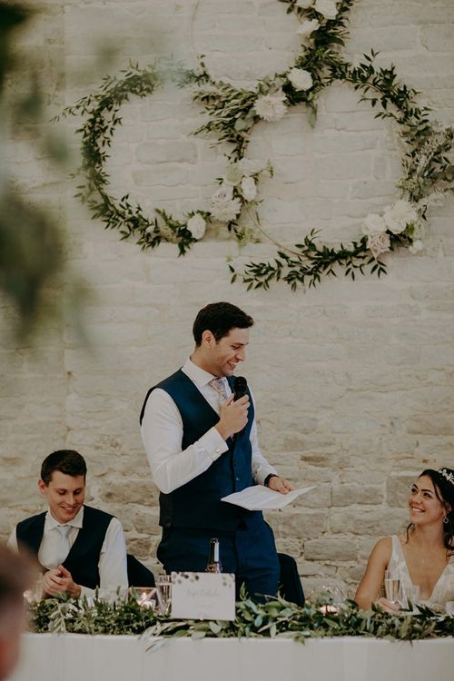 Groom wedding speech with hoop decor