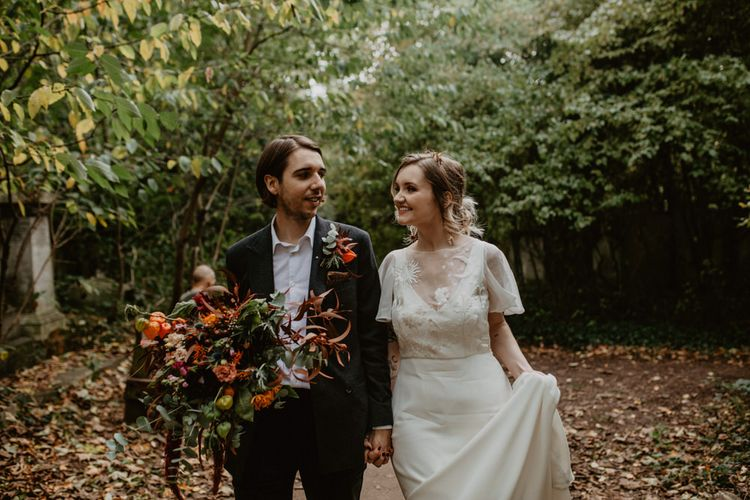 Bride and Groom Wedding Picture with Autumnal Leaves on the Floor