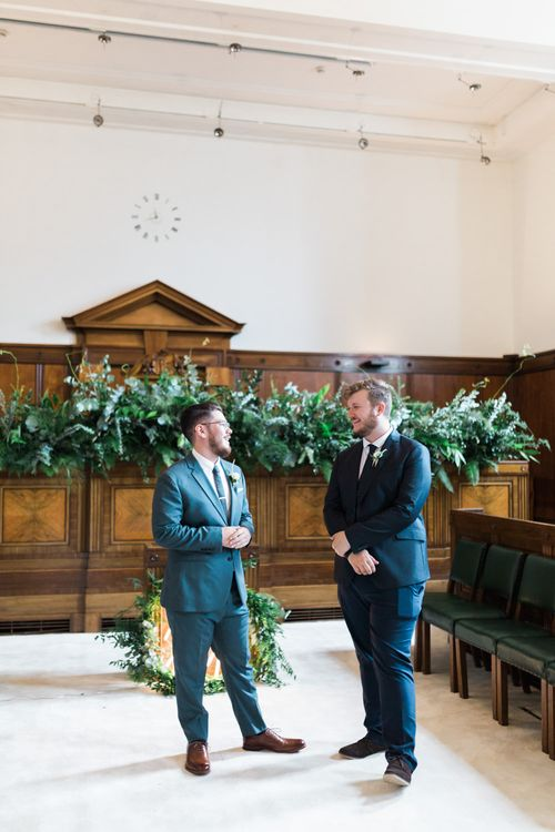 Groom in Blue Reiss Suit with Brown Grenson Shoes | Best Man in Navy Suit with Le Colonel Moutarde Tie | Neon You & Me Sign at Altar | Town Hall Hotel Bethnal Green | Neon Sign and Marine Green Rewritten Bridesmaids Dresses with Lace Cape Grace Loves Lace Gown | Alain Mbouche Photography