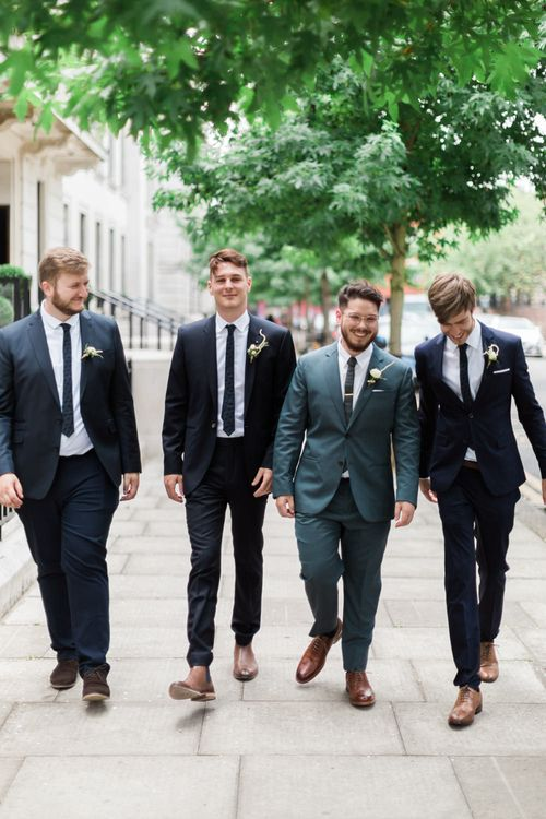 Groom in Blue Reiss Suit with Brown Grenson Shoes | Groomsmen in Navy Suits with Le Colonel Moutarde Ties | Neon Sign and Marine Green Rewritten Bridesmaids Dresses with Lace Cape Grace Loves Lace Gown | Alain Mbouche Photography