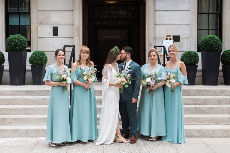 Bride in Grace Loves Lace Verdelle Dress with V-Neck, Low Square Back, Mid-Thigh Front Split and Lace Cape | Foliage Hair Crown | Gold Flat Gianvito Rossi Sandals | Groom in Blue Reiss Suit with Brown Grenson Shoes | Bridesmaids in Mismatched Marine Green Rewritten Dresses | Pastel Wedding Bouquets | Neon Sign and Marine Green Rewritten Bridesmaids Dresses with Lace Cape Grace Loves Lace Gown | Alain Mbouche Photography