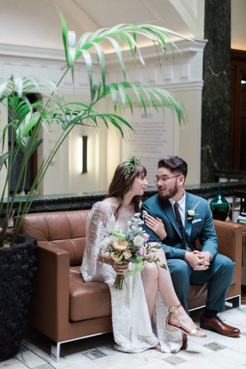 Bride in Grace Loves Lace Verdelle Dress with V-Neck, Low Square Back, Mid-Thigh Front Split and Lace Cape | Foliage Hair Crown | Gold Flat Gianvito Rossi Sandals | Pastel Bridal Bouquet | Groom in Blue Reiss Suit with Brown Grenson Shoes | Town Hall Hotel Bethnal Green | Neon Sign and Marine Green Rewritten Bridesmaids Dresses with Lace Cape Grace Loves Lace Gown | Alain Mbouche Photography