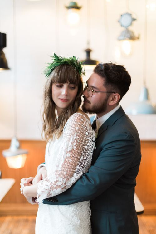 Bride in Grace Loves Lace Verdelle Dress with V-Neck, Low Square Back, Mid-Thigh Front Split and Lace Cape | Foliage Hair Crown | Groom in Blue Reiss Suit with Brown Grenson Shoes | Neon Sign and Marine Green Rewritten Bridesmaids Dresses with Lace Cape Grace Loves Lace Gown | Alain Mbouche Photography