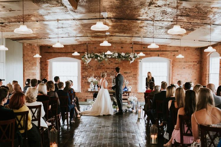 Bride and Groom Standing at the Altar  at TheirThe West Mill Wedding Venue
