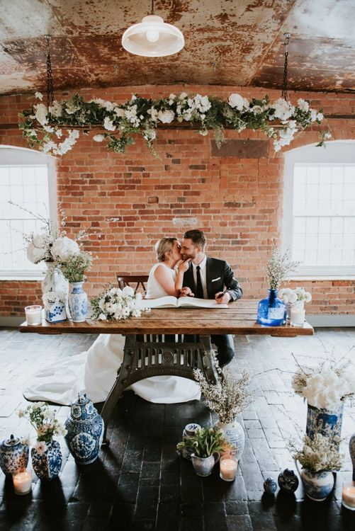 Bride and Groom Signing The Register with White and Blue Wedding Decor