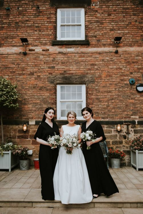 Bridal Party Portrait with Bride in Organza Wedding Dress and Bridesmaids in Black Wrap Dresses