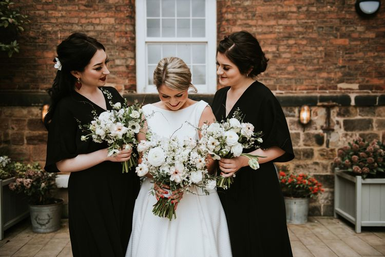 Bridesmaids in Black Wrap Dresses and Bride in Minimalist Wedding Dress from Serendipity Brides