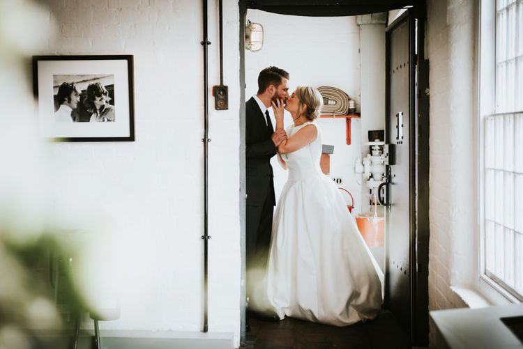 Bride and Groom Kissing in the Doorway