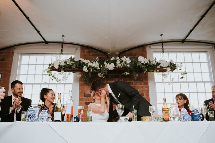 Bride and Groom Kissing at the Top Table with White Floral Installation