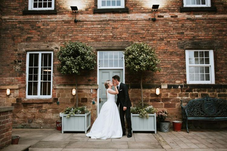 Bride and Groom Kissing in Front of Topiary Trees at The West Mill Wedding Venue