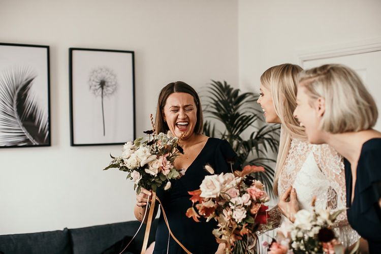 Bridesmaids in black dresses with pink floral bouquets