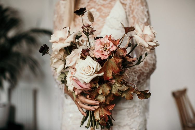 Lace and beaded boho bridal dress with tassel detailing and a pink bouquet