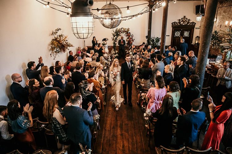 Bride and groom tie the knot at Clapton Country Club wedding ceremony with botanical styling and festoon lighting