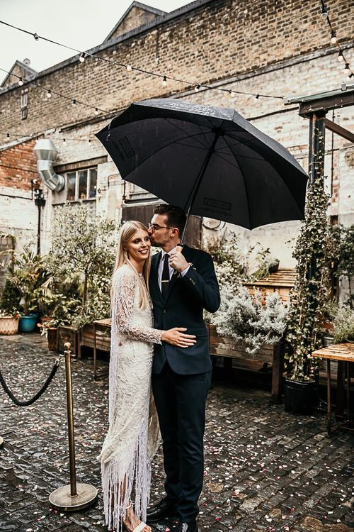 Bride wearing a lace and beaded boho style dress embraces with groom in Ted Baker suit