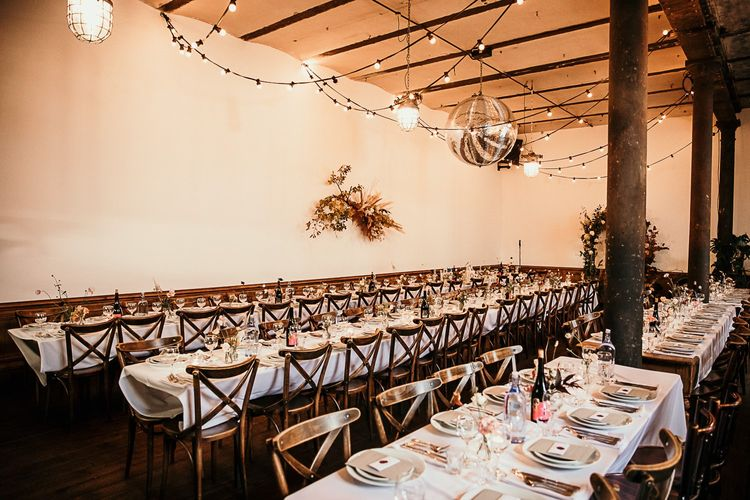 Reception decor with floral installations and festoon lighting at Clapton Country Club wedding