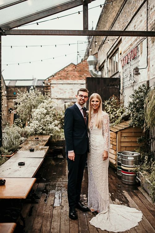 Bride and groom embrace at city celebration with botanical styling and foliage decor in East London